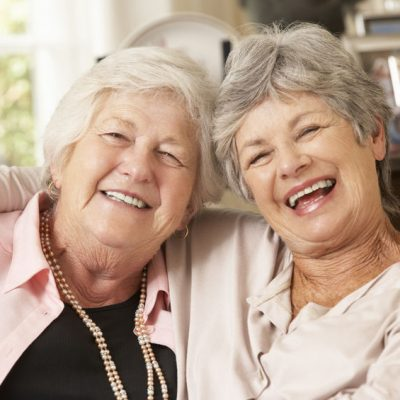 Two smiling women with osteoporsis and dental implants